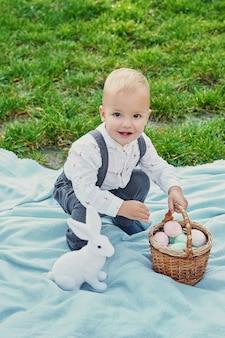 Menino com coelho e ovos para a páscoa no parque na grama verde