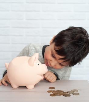 Menino com cofrinho de porco. infância, dinheiro, investimento e conceito de pessoas felizes