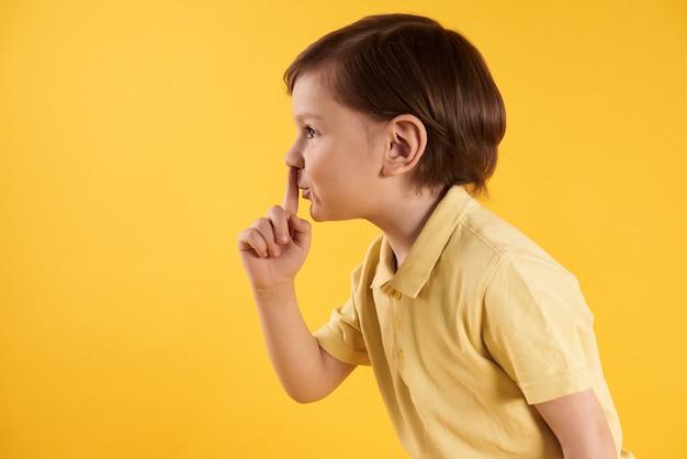 Menino, com, dedo indicador, em, boca, mostra, sinal, quietamente