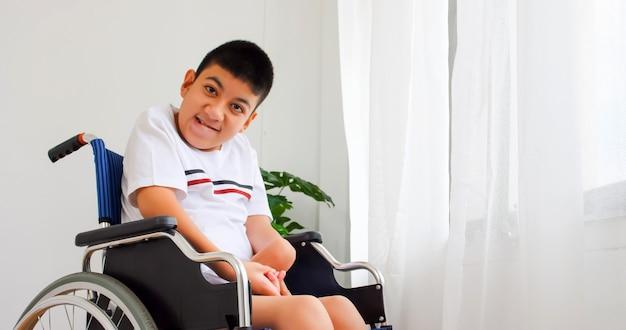 Menino com deficiência em cadeira de rodas.