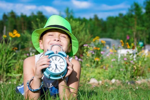 Menino com despertador coloca no jardim de verão