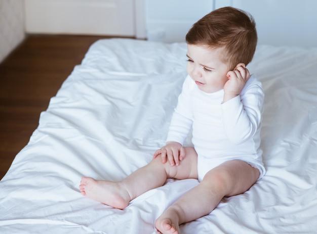 Menino com dor de ouvido gemendo segurando a mão na orelha em casa, dor de cabeça infantil, conceito de cuidados de saúde, proteção de ouvido, visão lateral de dor nos dentes