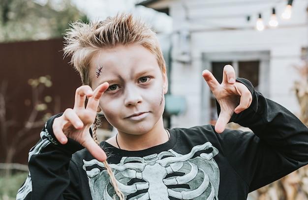 Menino com fantasia de esqueleto e rosto pintado na varanda de uma casa decorada para celebrar uma festa de halloween