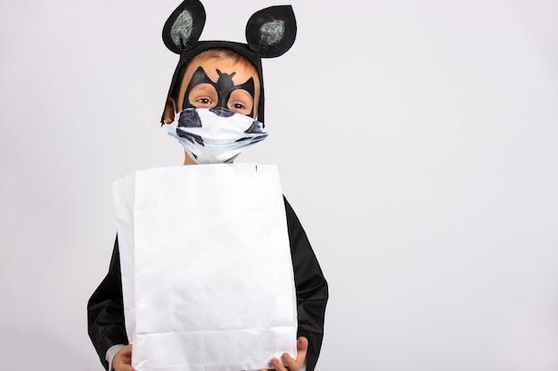 Menino com fantasia de morcego segurando um saco branco de chocolates com espaço em branco. criança com máscara médica na parede cinza.