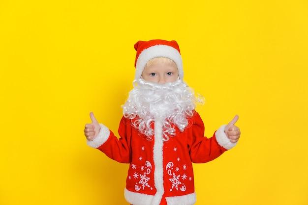Menino com fantasia de papai noel com barba branca mostrando o polegar para cima gesto com as mãos
