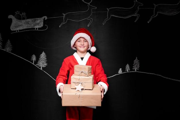 Menino com fantasia de papai noel dando uma pilha de presentes