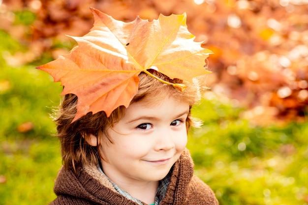 Menino com folhas de outono