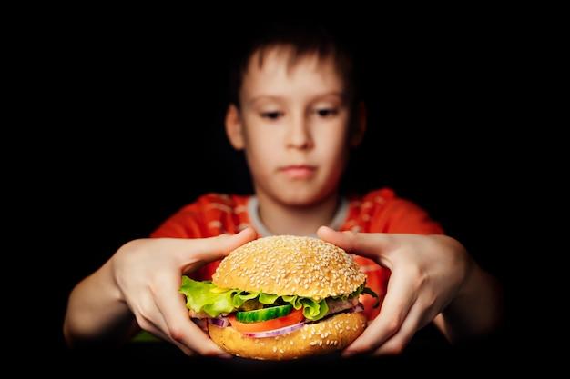 Menino com fome, segurando o hambúrguer de dar água na boca, isolado no escuro
