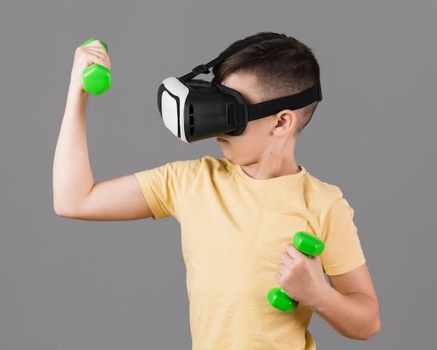 Menino com fone de ouvido de realidade virtual segurando pesos