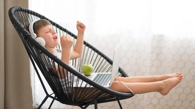 Menino com fones de ouvido e laptop na cadeira
