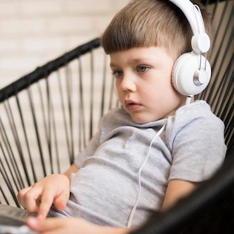 Menino com fones de ouvido e laptop