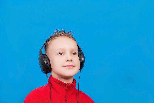 Menino com fones de ouvido em uma superfície azul
