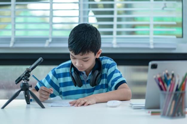 Menino com fones de ouvido está usando um tablet e se comunica pela internet em casa