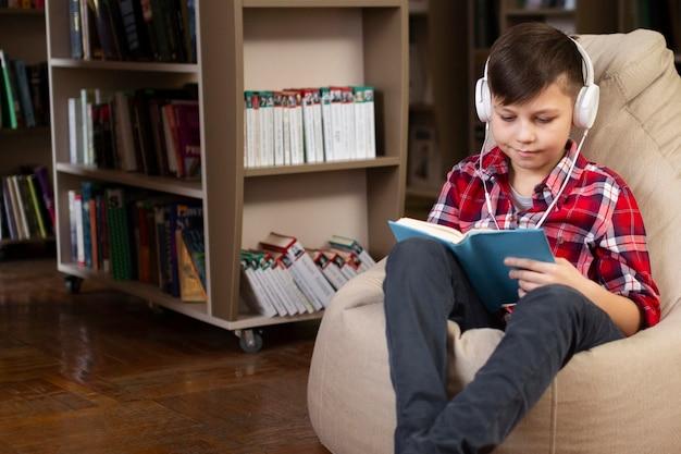 Menino com fones de ouvido lendo