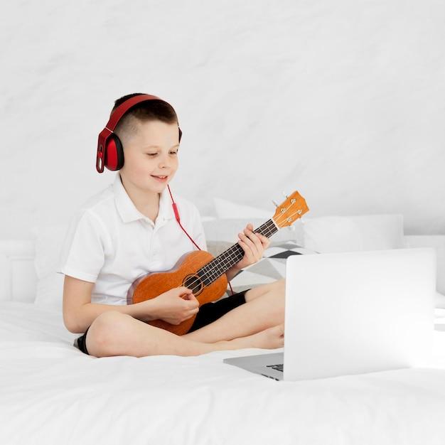 Menino com fones de ouvido tocando ukulele e sentado na cama