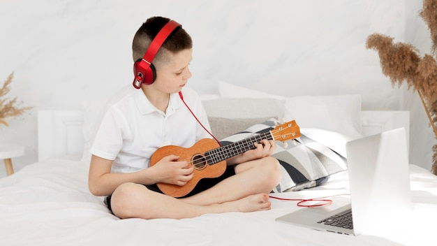 Menino com fones de ouvido tocando ukulele