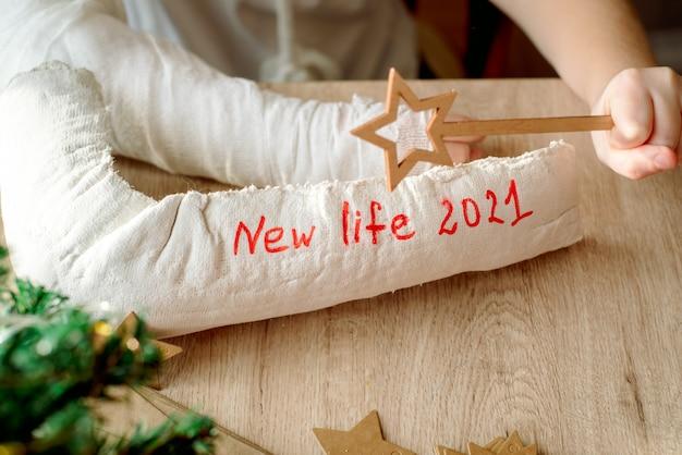 Menino com gesso no braço faz artesanato de natal. fratura e lesão na mão. remove o gesso, esperando uma nova vida. ano novo e novos planos.
