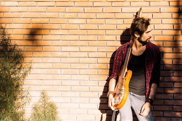 Menino, com, guitarra elétrica, por, parede tijolo
