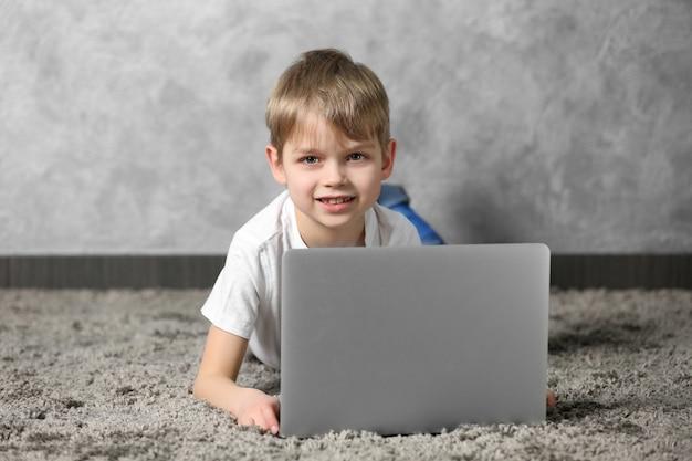 Menino com laptop no tapete de pele contra a superfície da parede cinza
