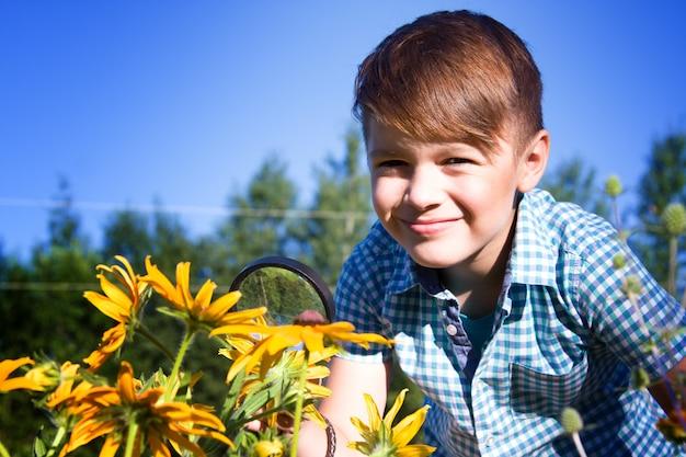 Menino com lupa no jardim de verão