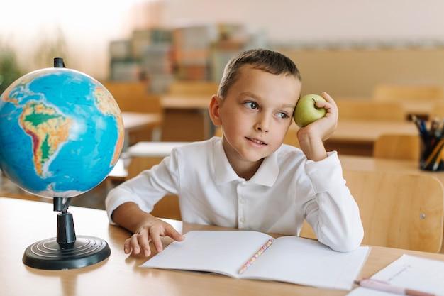 Menino com maçã na mesa na escola