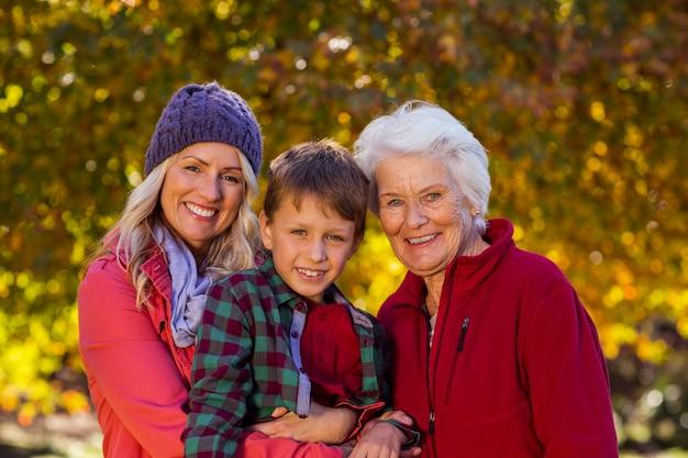 Menino com mãe e avó no parque