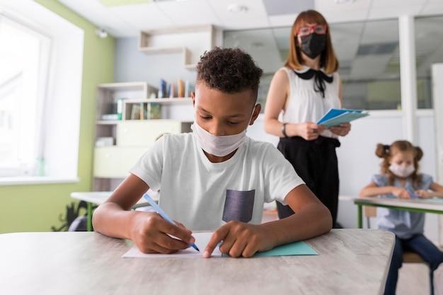 Menino com máscara médica escrevendo