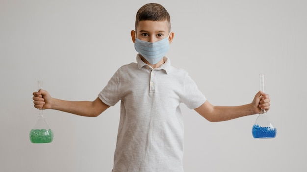 Menino com máscara médica segurando elementos químicos em recipientes
