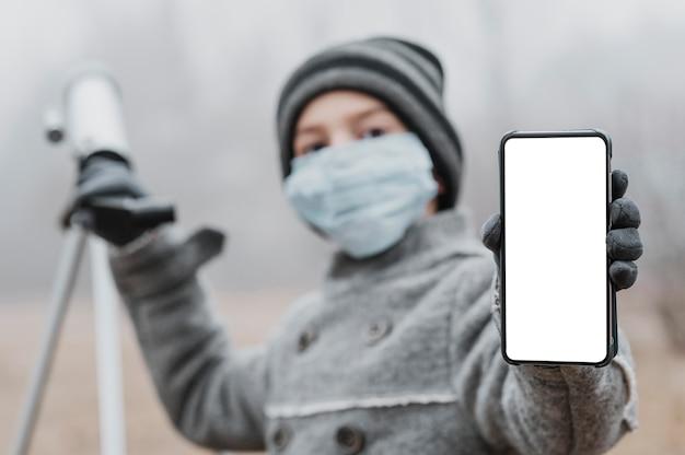 Menino com máscara médica usando um telescópio e segurando um smartphone em branco