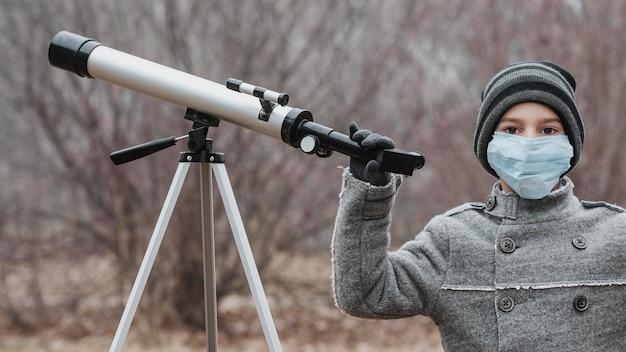 Menino com máscara médica usando um telescópio