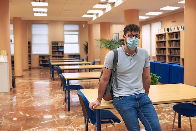 Menino com máscara olha para a câmera com uma biblioteca vazia ao fundo