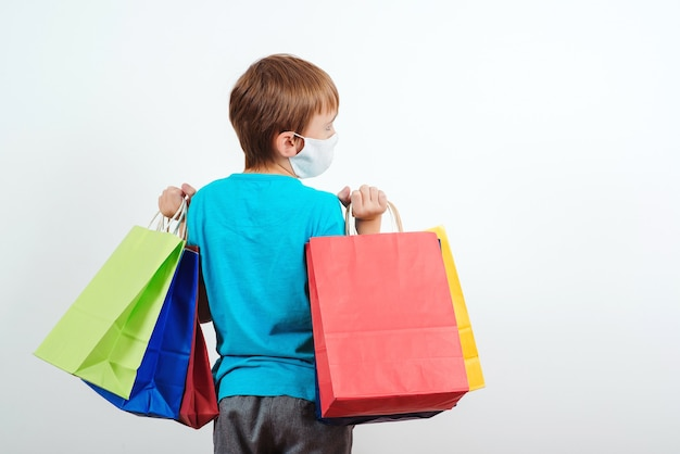 Menino com máscara protetora segurando sacolas de compras.