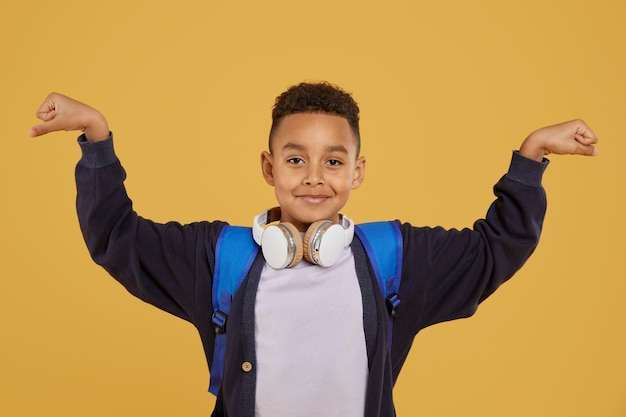Menino com mochila azul mostrando músculos