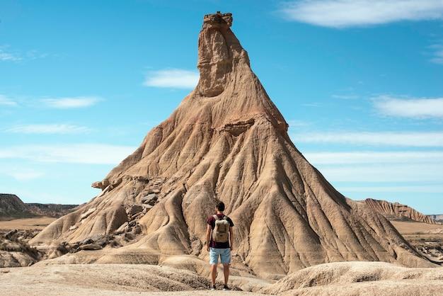 Menino com mochila e calça jeans viajando na paisagem desértica de bardenas reales navarra