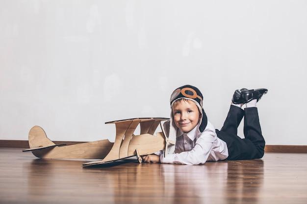 Menino com modelo de avião de madeira e boné com boné