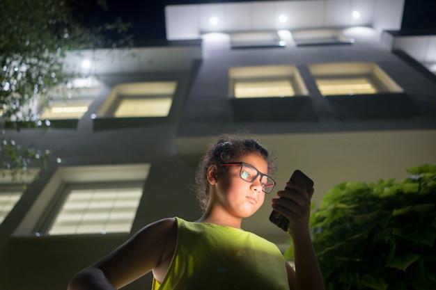 Menino com modile na frente da casa à noite