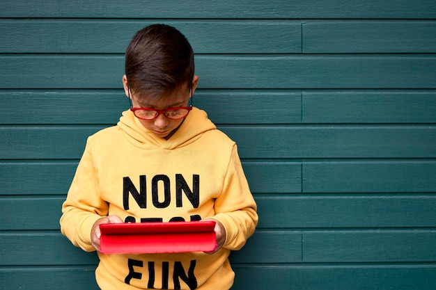 Menino com moletom amarelo surfando com seu tablet. fundo verde de madeira