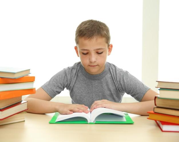 Menino com muitos livros na escola