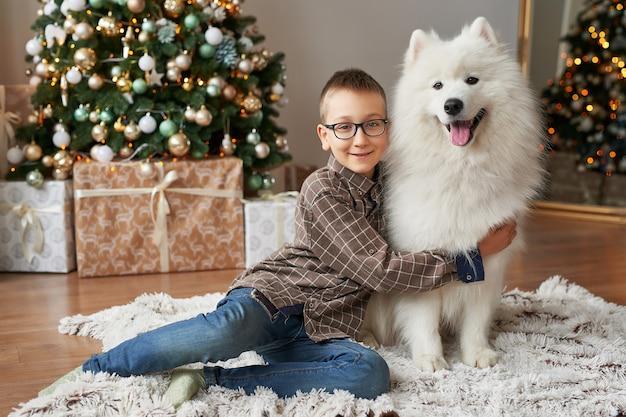 Menino com o cão perto da árvore de natal no fundo do natal