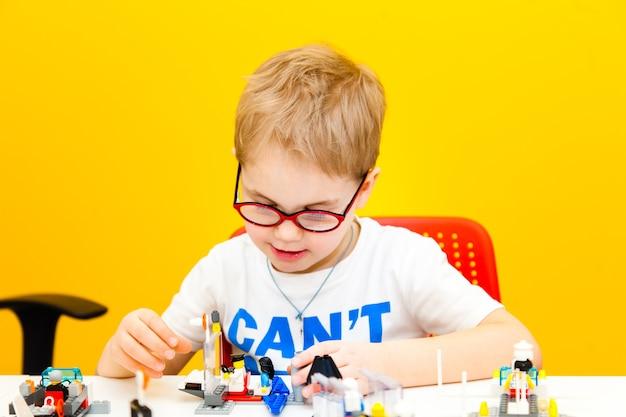 Menino com óculos brincando com blocos de brinquedo de construção em casa