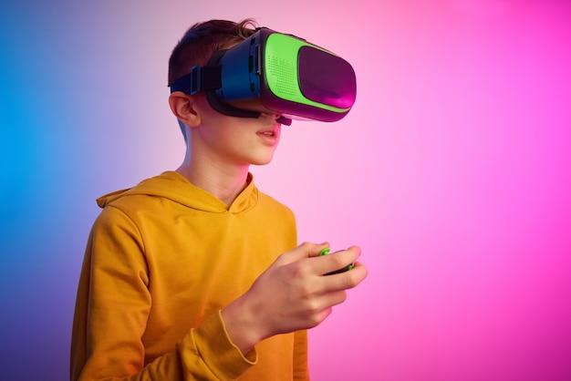 Menino com óculos de realidade virtual em parede colorida