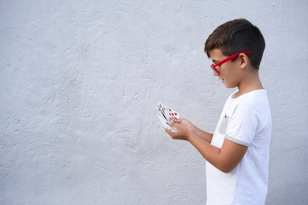 Menino com óculos de sol vermelhos jogando pôquer