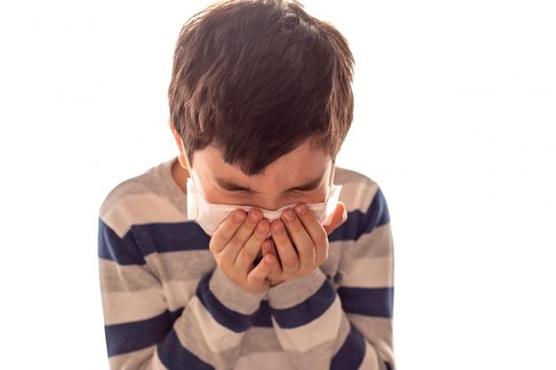 Menino com os olhos fechados espirra ou tosse nas mãos. gripe