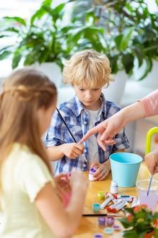 Menino com pincel. garoto loiro segurando uma escova de pintura na aula na escola, enquanto está perto de uma garota
