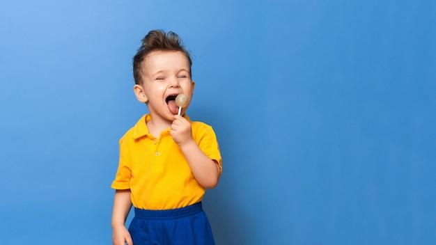 Menino com pirulito em pé sobre um fundo de parede azul