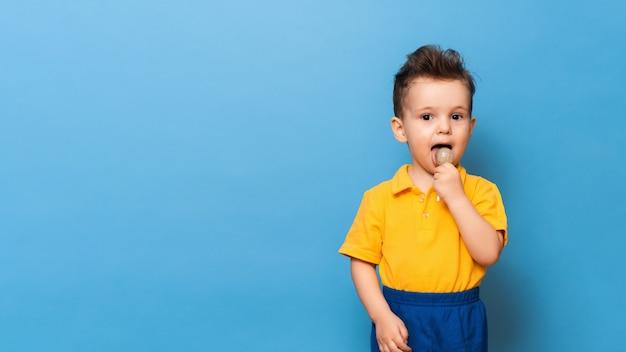 Menino com pirulito fica em uma parede azul. prevenção da cárie infantil. copie o espaço