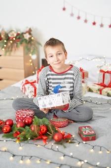 Menino com presentes de natal em casa na cama com decoração de natal