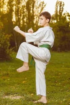 Menino com quimono branco durante o treinamento de exercícios de caratê ao ar livre no verão