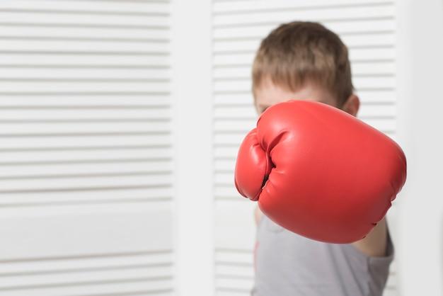 Menino com raiva na luva de boxe vermelha. acertar