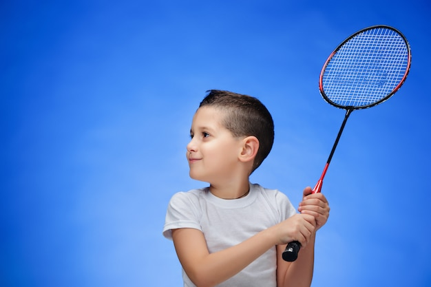 Menino com raquetes de badminton ao ar livre